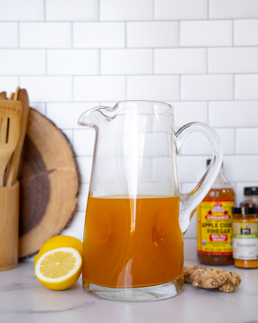 Pitcher of Super Youth Apple Cider Vinegar Detox Recipe with ingredients in the background